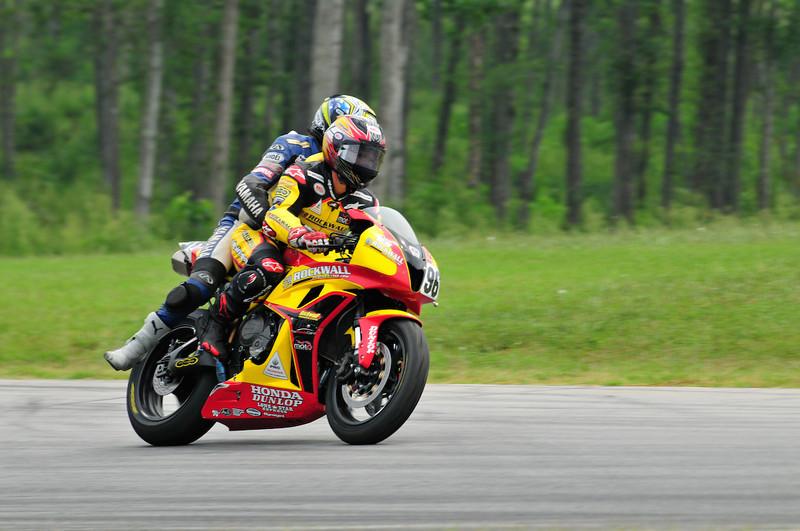 Aaron Gobert gives a fallen Yamaha rider a lift after the Supersport race.