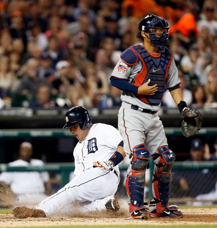 . Detroit Tigers\' Miguel Cabrera scores as Minnesota Twins catcher Kurt Suzuki, right, waits for a throw on a Victor Martinez single in the fourth inning of a baseball game in Detroit, Friday, Sept. 26, 2014. (AP Photo/Paul Sancya)