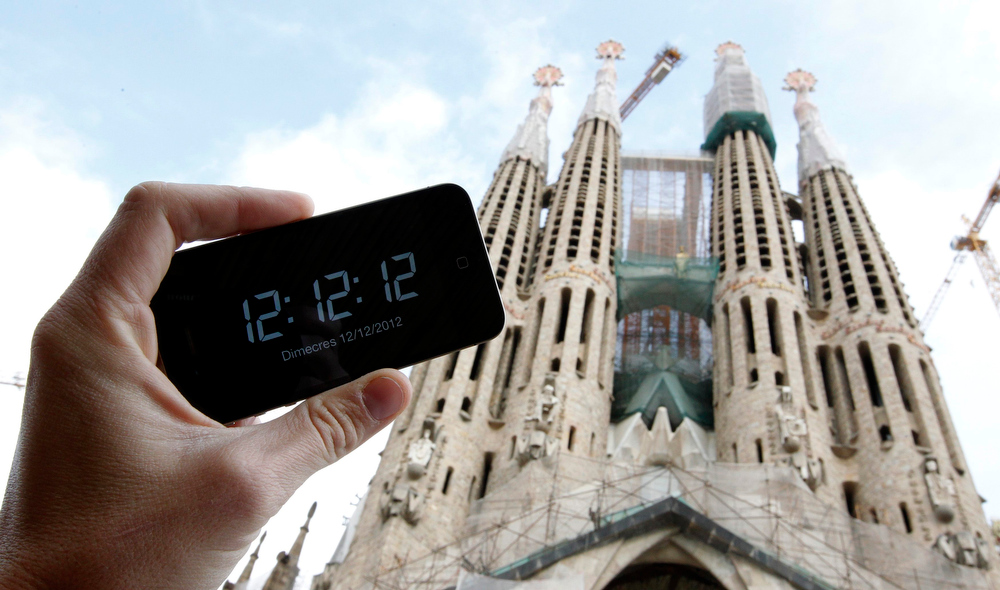 Description of . A photographer pictures his mobile phone reading 12:12:12 in front the Basilica Sagrada Familia designed by Catalan modernist architect Antonio Gaudi in Barcelona December 12, 2012. Wednesday December 12, 2012 is the lat day in this century where the numeral date can be all the same number. REUTERS/Albert Gea