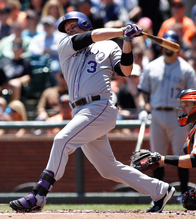 . Colorado Rockies\' Michael Cuddyer hits a two-RBI double against the San Francisco Giants during the first inning of a baseball game on Sunday, May 26, 2013, in San Francisco. Giants\' Buster Posey, front right, looks on. (AP Photo/George Nikitin)