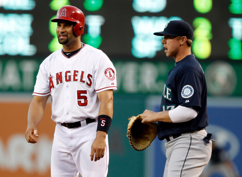 . Los Angeles Angels\' Albert Pujols (5) enjoys a moment at first with Seattle Mariners first baseman Justin Smoak, right, in the first inning during a baseball game Tuesday, May 21, 2013 in Anaheim.    (AP Photo/Alex Gallardo)
