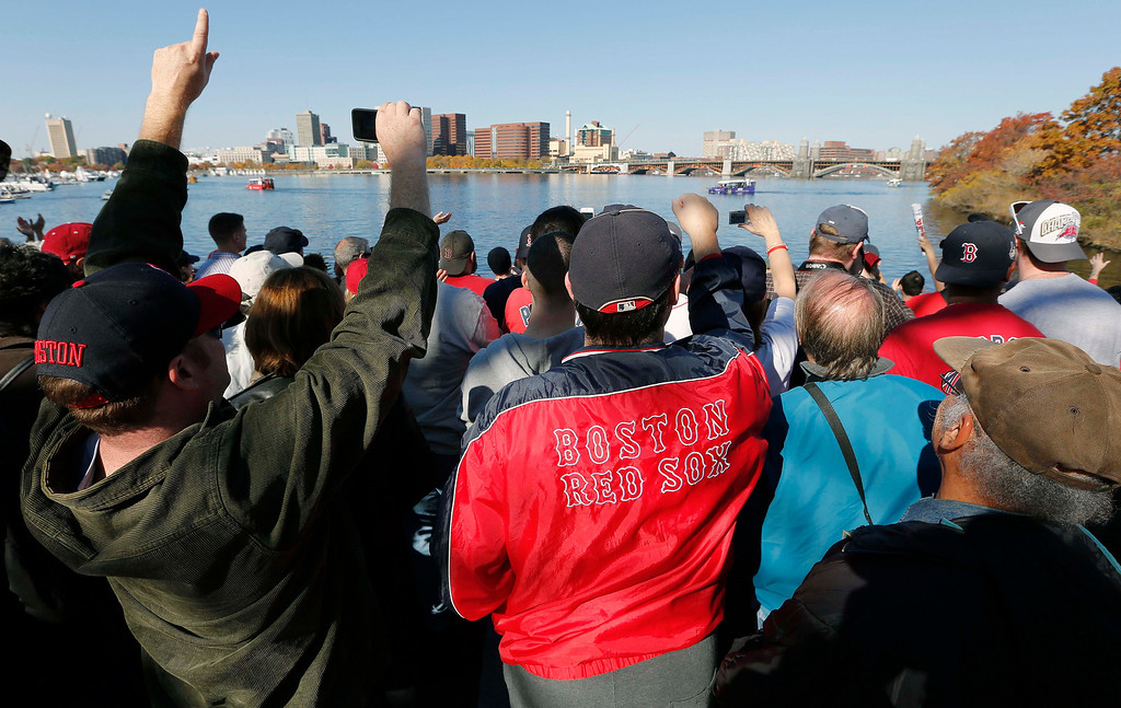. Boston Red Sox fans line the banks of the Charles River as players pass by on duck boats during a rolling victory parade celebrating the baseball team\'s World Series title, Saturday, Nov. 2, 2013, in Boston. (AP Photo/Michael Dwyer)