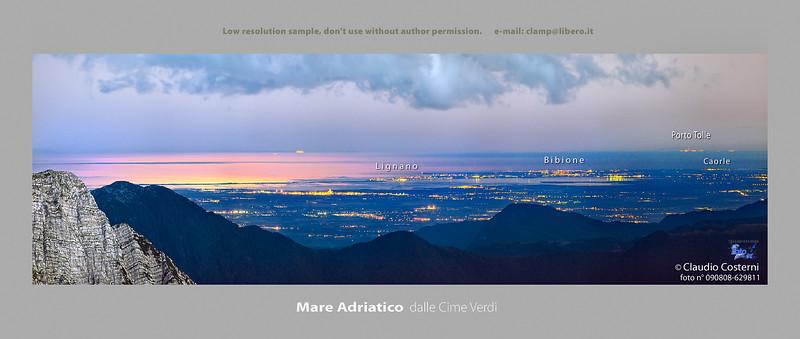Il mare Adriatico e la pianura Friulana, in una fresca e limpida notte di agosto.  Luogo di osservazione: le Cime Verdi, di fronte al Mangart.   L' ampia area giallo-arancio sul mare è creata dal riflesso della luce della luna fuori dall' inquadratura.  L' aria è così limpida che si vedono distintamente le luci di Porto Tolle, alle foci del fiume Po, ad oltre 200 km di distanza!