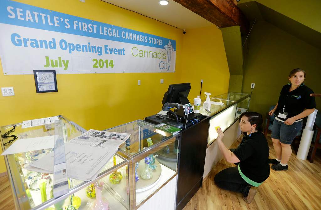 . Amber McGowan, left, and Krystal Klacsan, right, work Monday, July 7, 2014 at the recreational marijuana store Cannabis City in Seattle to apply a state-mandated frosted film to the front of a display case that will contain pot varieties when legal sales begin on Tuesday, July 8, 2014. The store will be the first and only store in Seattle to initially sell recreational marijuana on Tuesday. (AP Photo/Ted S. Warren)