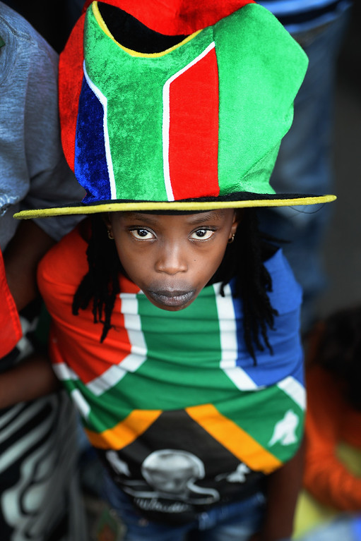 . A child stands with ANC supporters who were singing and dancing to celebrate the life of Nelson Mandela outside his former home in Vilakazi Street, Soweto Township, on December 7, 2013 in Soweto, South Africa.  (Photo by Jeff J Mitchell/Gallo Images/Getty Images)