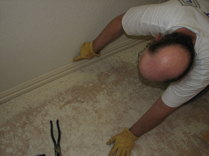 Using a utility knife to cut through some caulk. Note, use short strokes, otherwise you'll slip and cut the baseboard (experience talking)