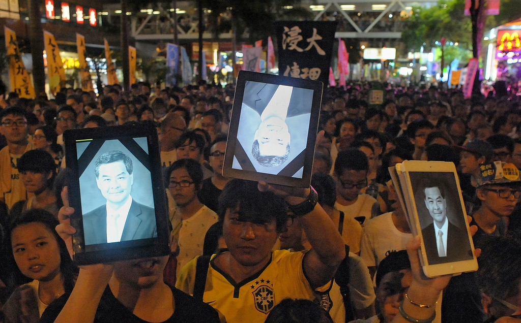 ". Protesters hold up tablet computers showing an image of Hong Kong\'s Chief Executive Leung Chun-ying similar to a funeral altar photo (with black band), while hundreds of thousands take part in a pro-democracy rally seeking greater democracy in Hong Kong on July 1, 2014 as frustration grows over the influence of Beijing on the city.  July 1 is traditionally a day of protest in Hong Kong and also marks the anniversary of the handover from Britain to China in 1997, under a ""one country, two systems\"" agreement.      RICHARD A. BROOKS/AFP/Getty Images"