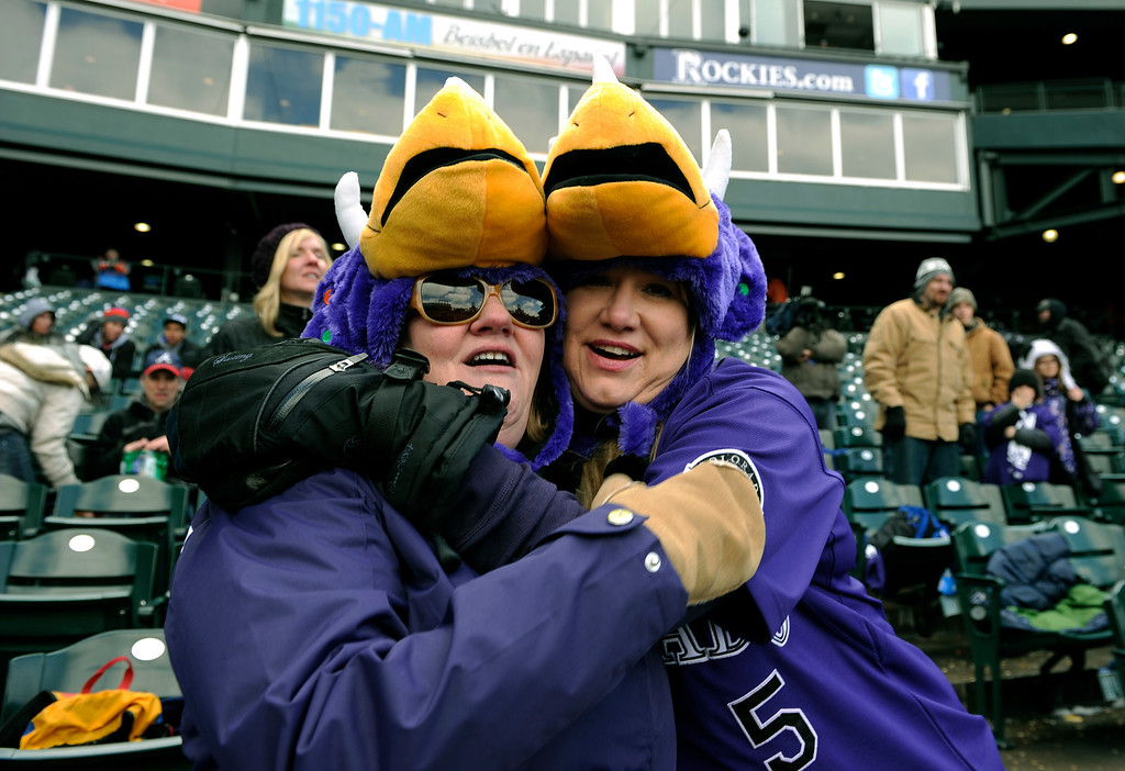 . DENVER, CO. - APRIL 23:  Best friends Luise Jackfest, left, and Dianna Shoemaker, right, huddled for warmth in the seventh inning. They bought the novelty hats in the gift shop to keep warm. The Atlanta Braves defeated the Colorado Rockies 4-3 at Coors Field Tuesday, April 23, 2013.  The first game of the doubleheader Tuesday was a make-up from Monday night\'s postponement due to weather.  Photo By Karl Gehring/The Denver Post