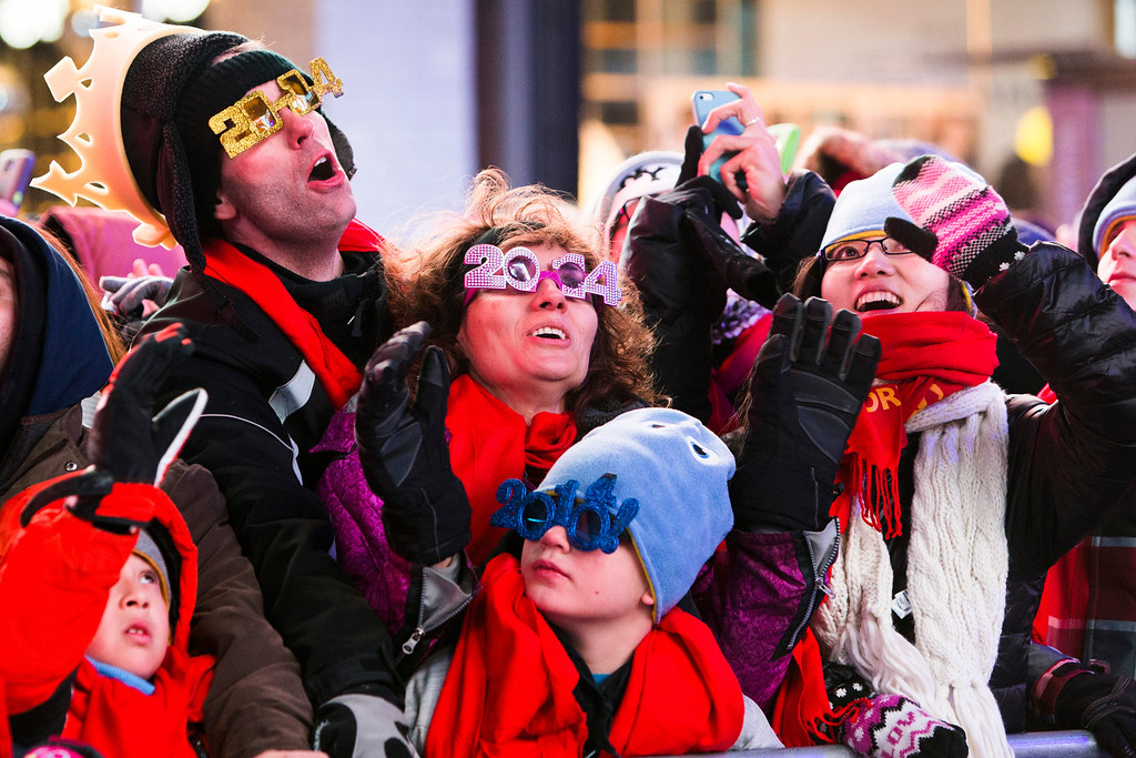 . NEW YORK, NY - DECEMBER 31: Revelers wait in New York\'s Times Square to celebrate the New Year on December 31, 2013 in New York City. Thousands of people have endured long hours of cold weather to have a front seat to this year\'s star studded celebration. (Photo by Christopher Gregory/Getty Images)