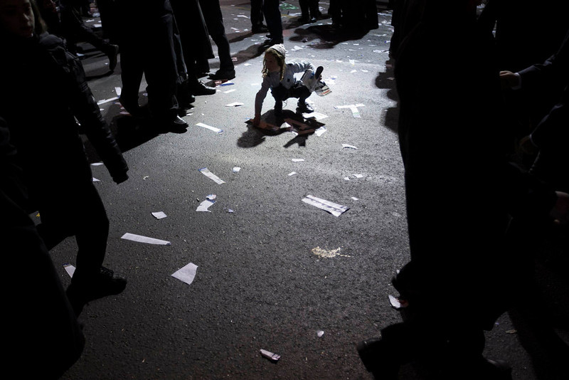 . An ultra-Orthodox Jewish boy picks up a sticker from the street during a rally organised to welcome Rabbi Zalman Leib Teitelbaum, in Jerusalem\'s Mea Shearim neighbourhood January 20, 2013. Local media said that Rabbi Zalman Leib Teitelbaum, son of the late Rabbi Moses Teitelbaum, leader of the Satmar Hasidim landed in Israel on Sunday for the wedding of his granddaughter which will take place later in the week. REUTERS/Ronen Zvulun