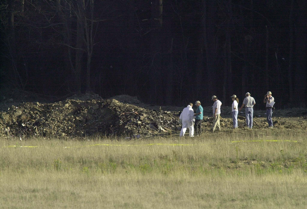 . Officials examine the crater 11 September 2001 at the crash site of United Airlines Flight 93 in Shanksville, Pennsylvania.  The plane from Newark, New Jersey, and bound for San Francisco, California, was hijacked and crashed in the field killing all 45 people on board.  AFP PHOTO/David MAXWELL