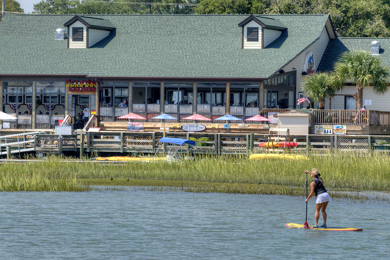 A woman paddleboards along the inlet near Dead Dog Saloon in Murrells Inlet, SC on Tuesday, September 10, 2013. Copyright 2013 Jason Barnette