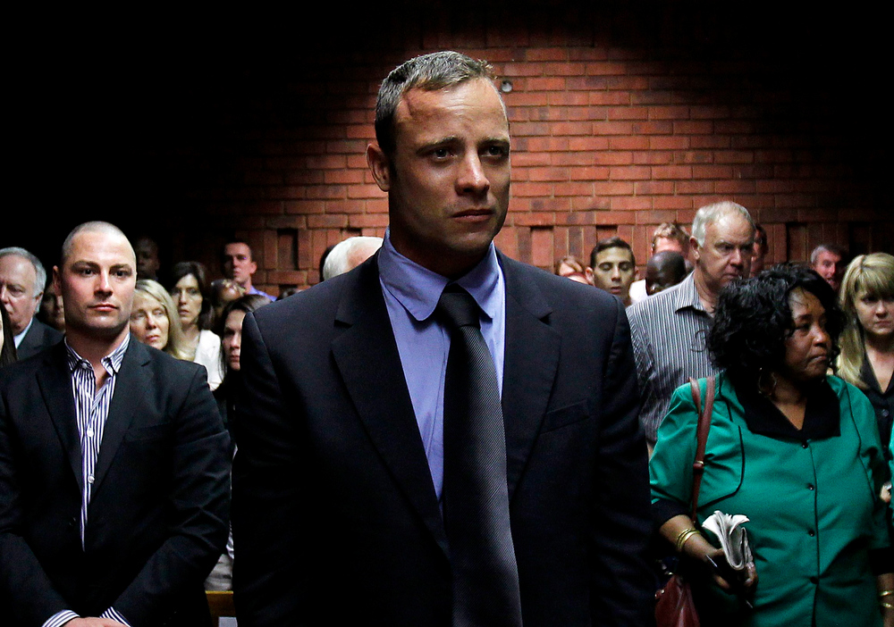 Description of . Oscar Pistorius awaits the start of court proceedings while his brother Carl (L) looks on, in the Pretoria Magistrates court February 19, 2013. Pistorius, a double amputee who became one of the biggest names in world athletics, was applying for bail after being charged in court with shooting dead his girlfriend, 30-year-old model Reeva Steenkamp, in his Pretoria house.REUTERS/Siphiwe Sibeko