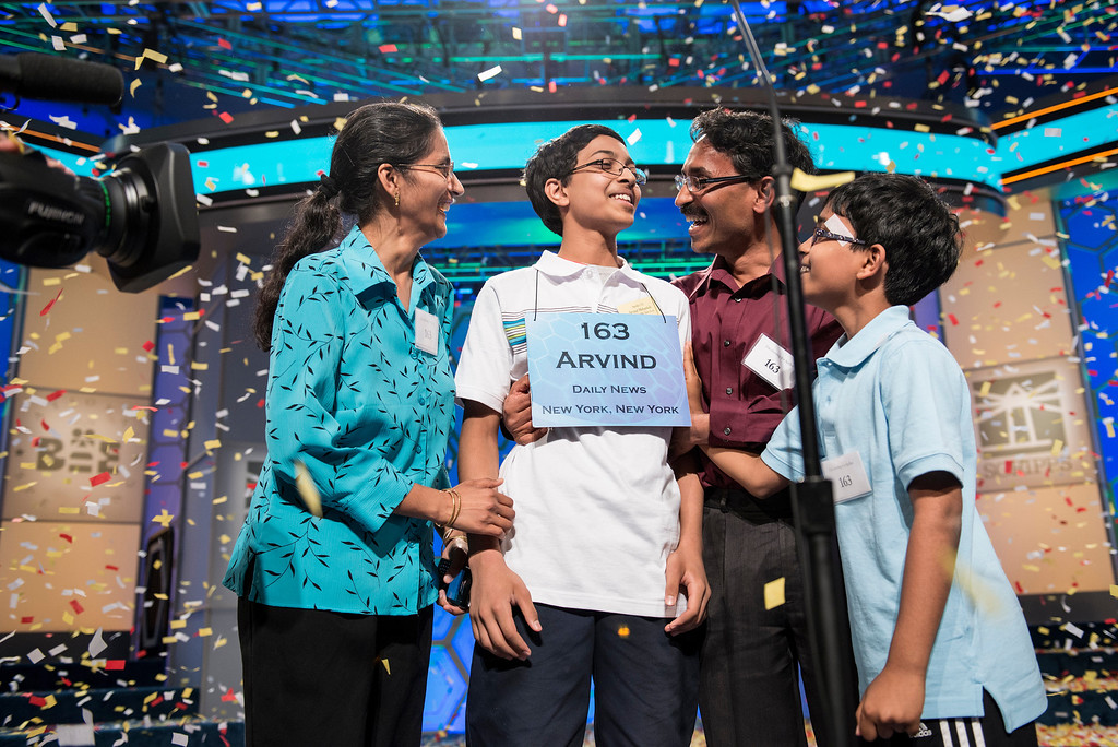 """. Arvind V. Mahankali (C), representing New York, is congratulated by his mother Bhavani Mahankali (L), father Srinivas Mahankali (2R) and brother Srinath Mahankali  (R) after winning the championship round at the Scripps National Spelling Bee May 30, 2013 in National Harbor, Maryland. Mahankali won by correctly spelling \""""knaidel\"""", a German-derived Yiddish word, defeating Pranav Sivakumar, representing Illinois. BRENDAN SMIALOWSKI/AFP/Getty Images"""