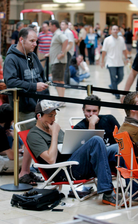 . Whitney George, left, and Gabriel George, right, surf the Internet on an Apple laptop while they wait in line for the opening of a new Apple store and the release of the new Apple  iPhone at Woodland Hills Mall in Tulsa, Okla., on Friday, June 29, 2007. The men waited about five hours for the store to open. (AP Photo/David Crenshaw)