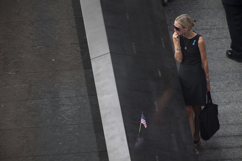 . A woman mourns at the names plaques at the 9/11 Memorial during ceremonies for the 12th anniversary of the terrorist attacks on lower Manhattan at the World Trade Center site on September 11, 2013 in New York City.  (Photo by Allan Tannenbaum-Pool/Getty Images)