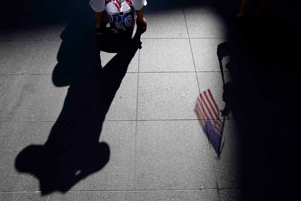 . A United States flag casts a shadow on the ground as spectators wait for a public reading the United States Declaration of Independence, part of Fourth of July Independence Day celebrations, in Boston, Massachusetts July 4, 2013. People across the United States gathered on Thursday for parades, picnics and fireworks at Independence Day celebrations, held under unprecedented security following the Boston Marathon bombings. Spectators waving U.S. flags and wearing red, white and blue headed for public gatherings in Boston, New York, Washington, Atlanta and other cities under the close watch of police armed with hand-held chemical detectors, radiation scanners and camera surveillance, precautions sparked by the deadly April 15 bombings.    REUTERS/Brian Snyder