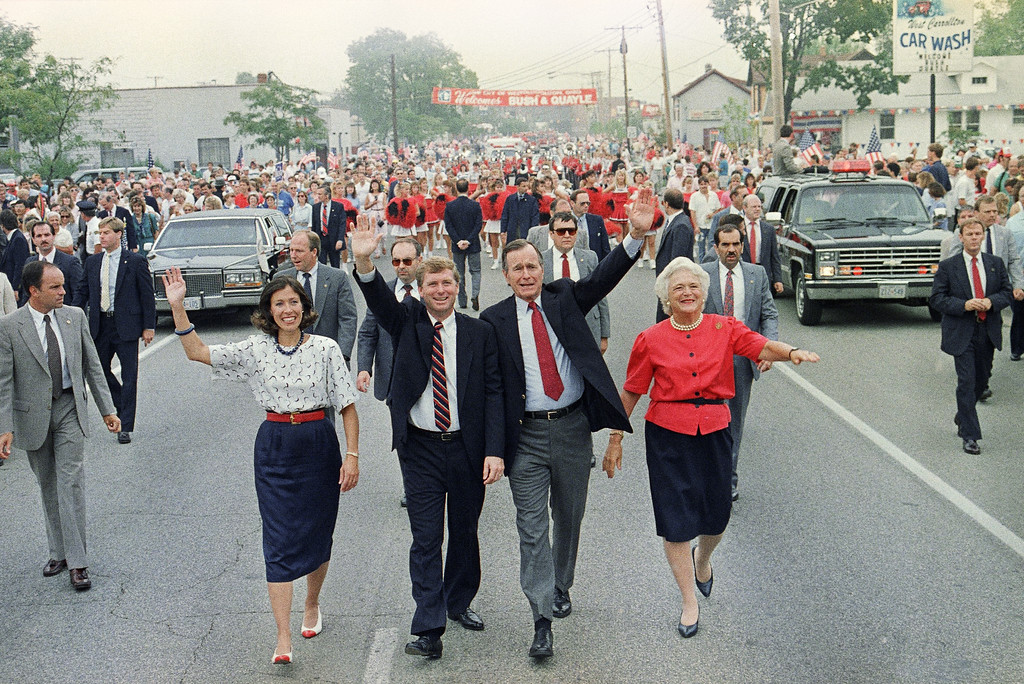 . Vice-President George Bush and his wife Barbara, right, march in the 4th Annual Paper Festival Parade with vice-presidential nominee Sen. Dan Quayle and his wife Marilyn in West Carrolltown, Ohio Saturday, August 20, 1988. (AP Photo/J. Scott Applewhite)