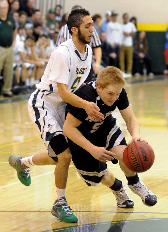 . Arapahoe guard Blake Nelson (5) dribbled past Golden Eagles defender Bashar Sawaged (4) in the second half. The Mountain Vista High School boy\'s basketball team defeated Arapahoe 69-54 Friday night January 4, 2013.  Karl Gehring/The Denver Post