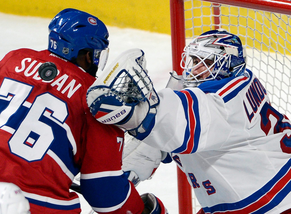 . New York Rangers goalie Henrik Lundqvist, right, reaches for a loose puck around Montreal Canadiens defenceman P.K. Subban (76) during the second period in Game 1 of the Eastern Conference finals in the NHL hockey Stanley Cup playoffs against in Montreal on Saturday, May 17, 2014. (AP Photo/The Canadian Press, Adrian Wyld)