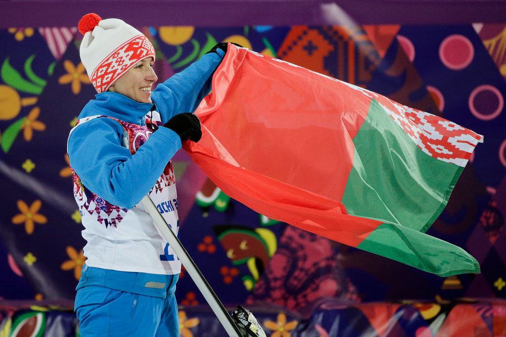 . Gold medalist Alla Tsuper, of Belarus, poses with a Belarusian flag after a flower ceremony for the women\'s freestyle skiing aerials final at the Rosa Khutor Extreme Park, at the 2014 Winter Olympics, Friday, Feb. 14, 2014, in Krasnaya Polyana, Russia. (AP Photo/Jae C. Hong)