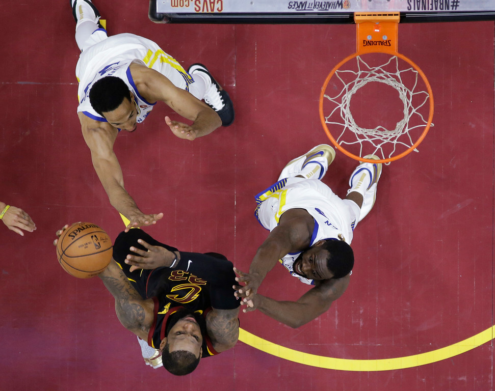 . Cleveland Cavaliers\' LeBron James shoots as Golden State Warriors\' Shaun Livingston, left, and Draymond Green defend during the first half of Game 3 of basketball\'s NBA Finals, Wednesday, June 6, 2018, in Cleveland. (AP Photo/Carlos Osorio, Pool)