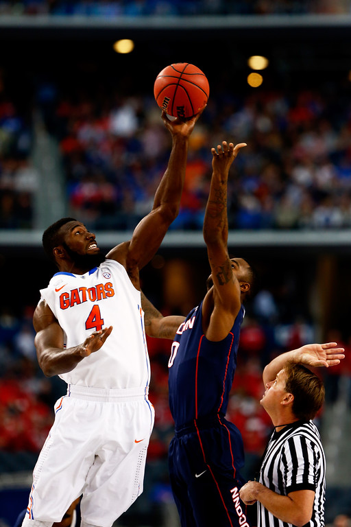 . ARLINGTON, TX - APRIL 05: Patric Young #4 of the Florida Gators and Phillip Nolan #0 of the Connecticut Huskies jump for the opening tip of the NCAA Men\'s Final Four Semifinal at AT&T Stadium on April 5, 2014 in Arlington, Texas.  (Photo by Tom Pennington/Getty Images)