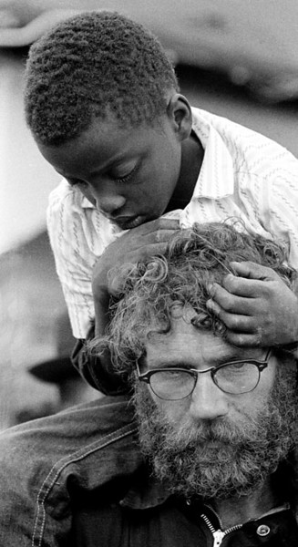 Canadian marcher with young injured negro boy on his shoulders.