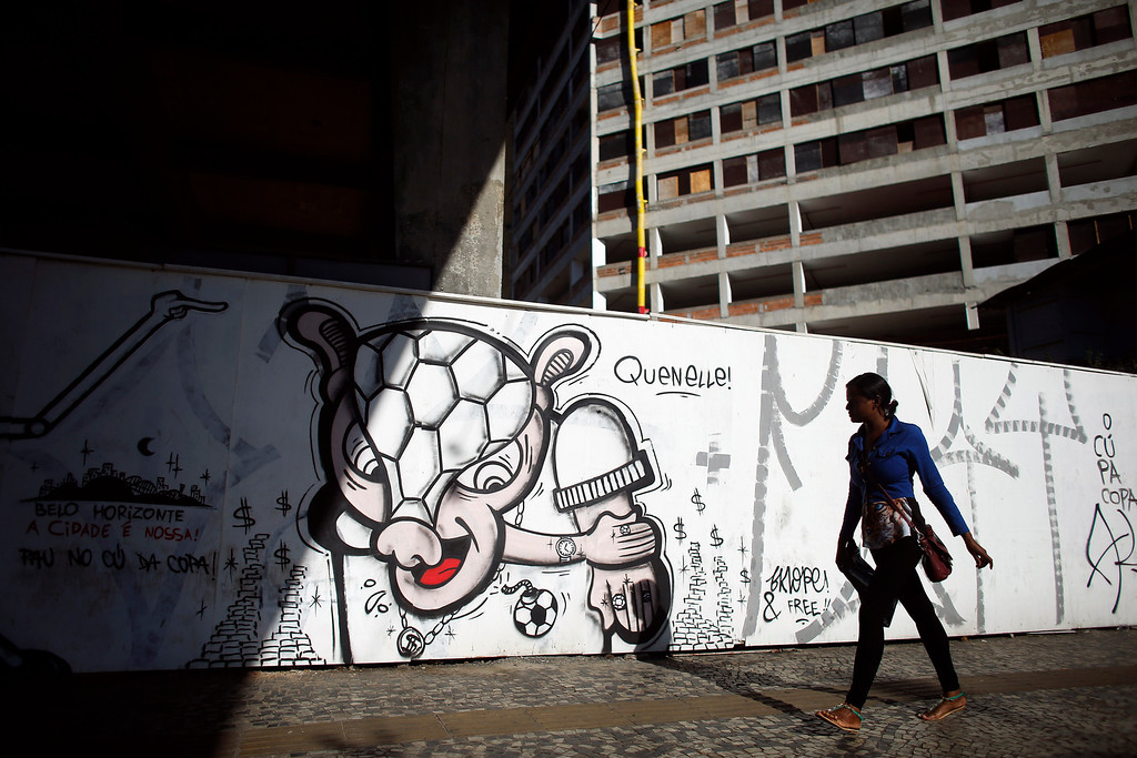 ". A woman walks by a mural depicting the World Cup mascot ""Fuleco\"" stealing money in Belo Horizonte, Brazil, Tuesday, June 10, 2014. There have been steady anti-government protests across Brazil blasting spending on the World Cup which starts June 12 and demanding improvements in woeful public services. (AP Photo/Victor R. Caivano)"