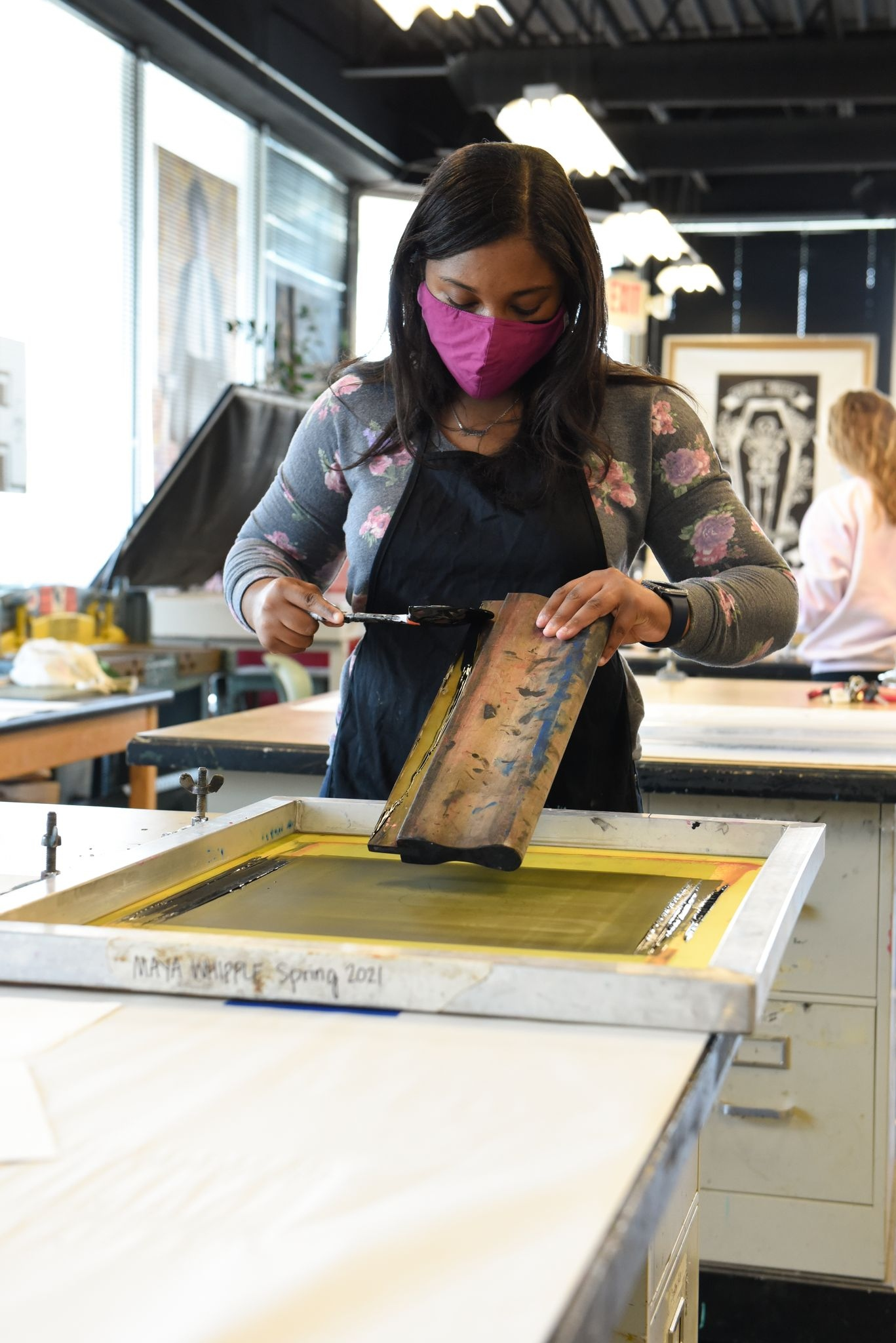 Junior Maya Whipple applies ink for a print.