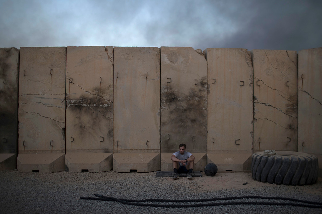 . An U.S. service member sits at a open air gym before Thanksgiving dinner at a coalition air base in Qayara south of Mosul, Iraq, Thursday, Nov. 24, 2016. (AP Photo/Felipe Dana)