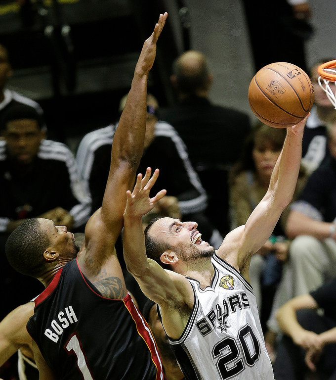 . San Antonio Spurs\' Manu Ginobili (20), of Argentina, attempts a shot as Miami Heat\'s Chris Bosh (1) defends during the second half at Game 5 of the NBA Finals basketball series, Sunday, June 16, 2013, in San Antonio. (AP Photo/David J. Phillip)