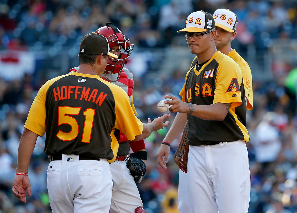 . U.S. Team pitcher Anthony Banda, of the Arizona Diamondbacks, is pulled by manager Trevor Hoffman (51) during the All-Star Futures baseball game against the World Team, Sunday, July 10, 2016, in San Diego. (AP Photo/Lenny Ignelzi)