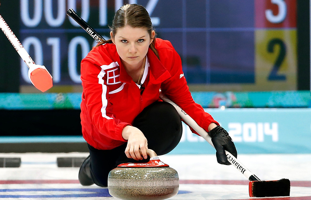 . Denmark\'s skip Lene Nielsen, delivers the rock while Maria Poulsen, right, sweeps the ice during the women\'s curling match against South Korea at the 2014 Winter Olympics, Sunday, Feb. 16, 2014, in Sochi, Russia. (AP Photo/Wong Maye-E)