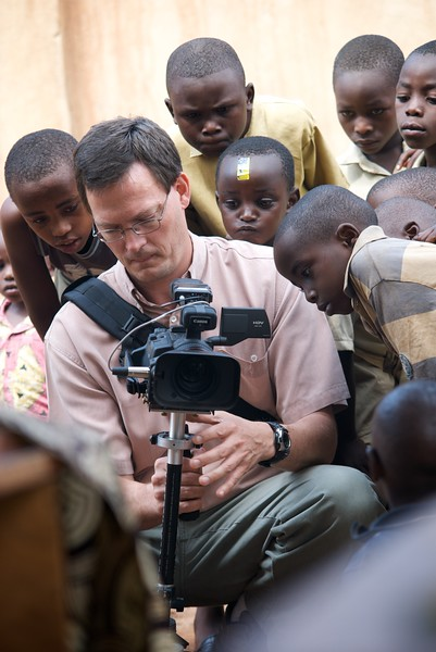 Ted Rurup filming with crowd of children watching  OFM team