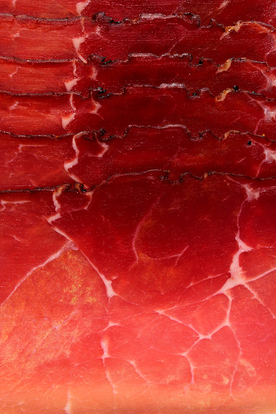 Smoked ham. Italian speck red meat slices isolated on studio background. Prosciutto beaf meat. Food photo.