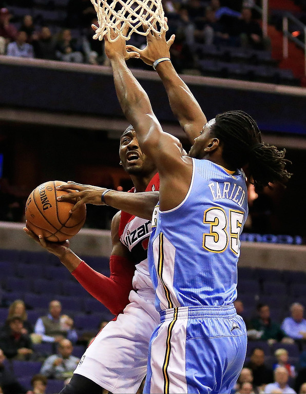 . John Wall #2 of the Washington Wizards puts up a shot in front of Kenneth Faried #35 of the Denver Nuggets during the first half at Verizon Center on December 9, 2013 in Washington, DC.  (Photo by Rob Carr/Getty Images)
