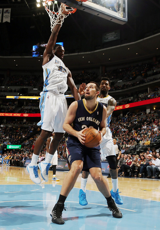 . New Orleans Pelicans forward Ryan Anderson, front, sets to take a shot as Denver Nuggets forwards Kenneth Faried, back left, and Wilson Chandler covers in the third quarter of the Nuggets\' 102-93 victory in an NBA basketball game in Denver on Sunday, Dec. 15, 2013. (AP Photo/David Zalubowski)