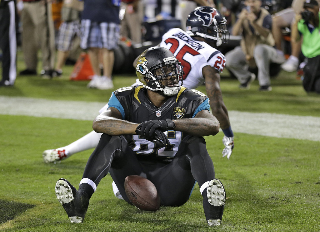 . Jacksonville Jaguars tight end Marcedes Lewis (89) reacts after catching a one-yard touchdown pass in front of Houston Texans cornerback Kareem Jackson (25) during the first quarter of an NFL football game Thursday, Dec. 5, 2013, in Jacksonville, Fla. (AP Photo/Chris O\'Meara)
