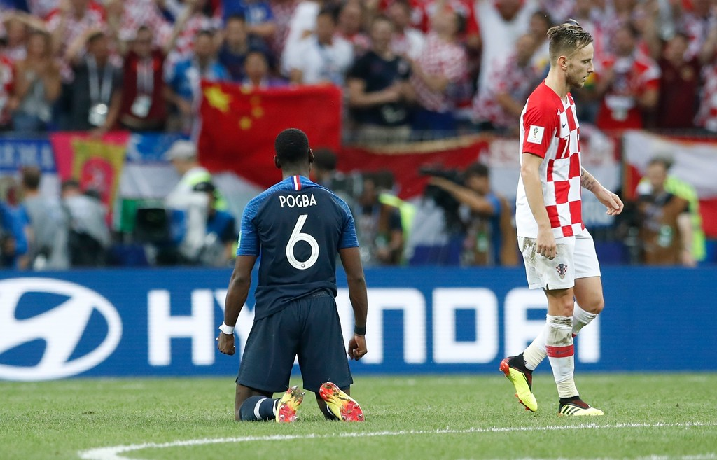. France\'s Paul Pogba kneels as Croatia\'s Ivan Rakitic walks past him, during the final match between France and Croatia at the 2018 soccer World Cup in the Luzhniki Stadium in Moscow, Russia, Sunday, July 15, 2018. (AP Photo/Petr David Josek)
