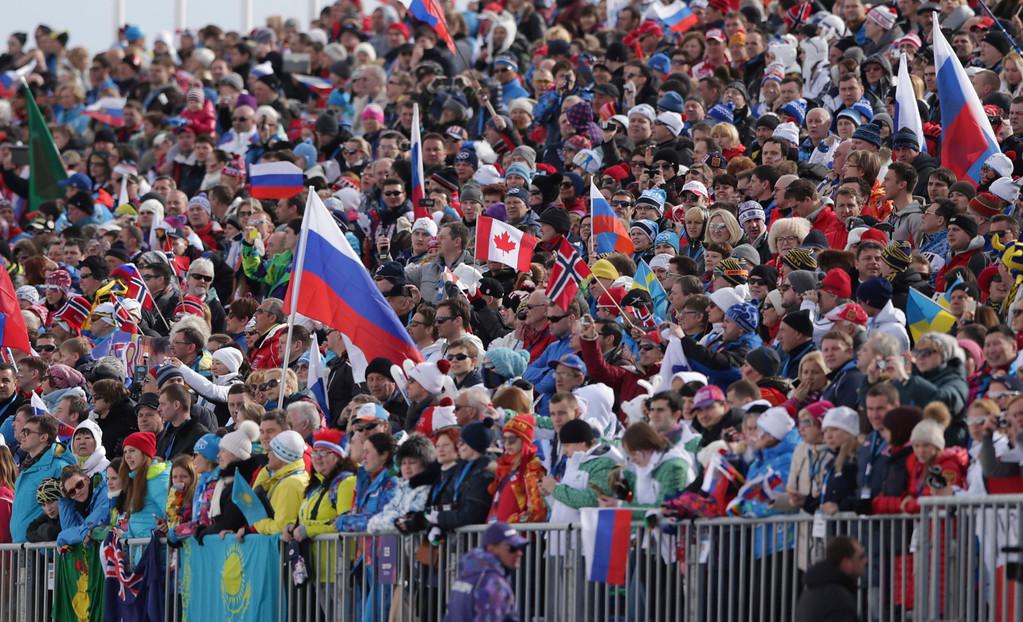 . Spectators watch the men\'s cross-country 30k skiathlon at the 2014 Winter Olympics, Sunday, Feb. 9, 2014, in Krasnaya Polyana, Russia. (AP Photo/Matthias Schrader)