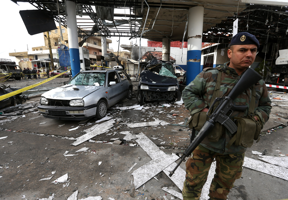 . A Lebanese army soldier, stand guard at the site of a deadly car bomb that exploded Saturday evening near a gas station, in the predominately Shiite town of Hermel, about 10 miles (16 kilometers) from the Syrian border in northeast Lebanon, Sunday, Feb. 2, 2014. (AP Photo/Hussein Malla)