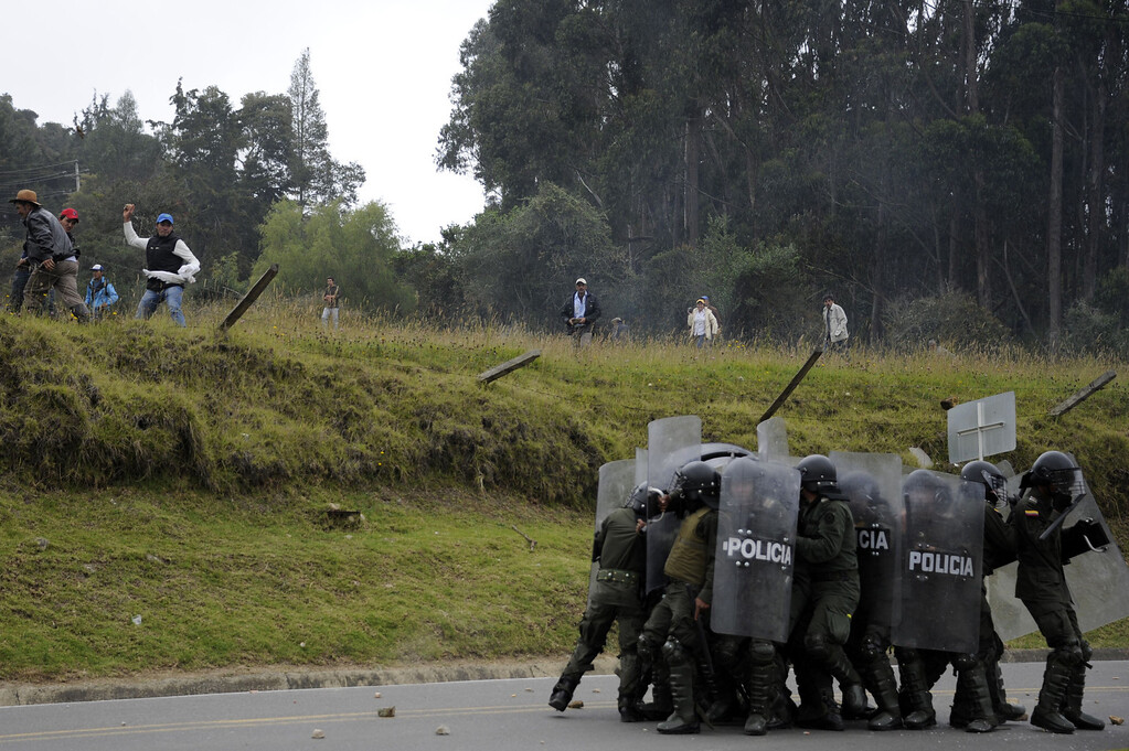 . Colombian farmers hurl stones at riot police during clashes at a road blockade in La Calera, Cundinamarca department, on August 23, 2013. A five-day-old farmworkers\' protest in Colombia claimed its first fatality Friday when a man on a motorcycle crashed and died at a roadblock, police said Friday. Since the protests began Monday, farmworkers have closed roads at dozens of points in across the country, blocking the passage of cargo trucks and other vehicles from makeshift camps erected on sides of roads. EITAN ABRAMOVICH/AFP/Getty Images