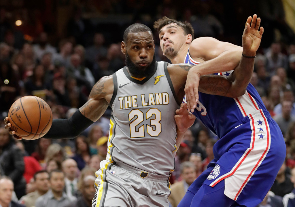 . Cleveland Cavaliers\' LeBron James (23) drives past Philadelphia 76ers\' Dario Saric (9), from Croatia, in the first half of an NBA basketball game, Thursday, March 1, 2018, in Cleveland. (AP Photo/Tony Dejak)