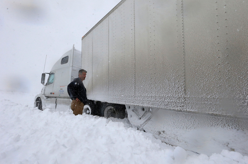 . Omer Odovsc looks over his tractor trailer that got stuck on the 219 off ramp leading to Rt. 391 in Boston, N.Y., Tuesday, Nov. 18, 2014. Parts of New York measured the season\'s first big snowfall in feet, rather than inches, on Tuesday as 3 feet of lake-effect snow blanketed the Buffalo area and forced the closure of a 132-mile stretch of the state Thruway. (AP Photo/The Buffalo News, Harry Scull Jr.)