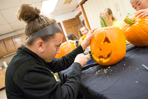 10/14/19 Wesley Bunnell | StaffrrVolunteers, many of them high school students and members of the Interact Club, carved pumpkins for the upcoming lighted jack-o-lantern trail walk coming up this Friday October 18th and October 19th at Hungerford Nature Center. Interact Club member Jenna Zup works on a traditional jack-o-lantern design.