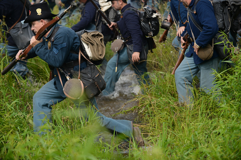 ". The 24th Michigan ""Iron Brigade\"" crosses a stream to pursue the Confederates at the Blue-Grey Alliance re-enactment battle held at the Bushey Farm on June 28, 2013. LEBANON DAILY NEWS - JEREMY LONG"