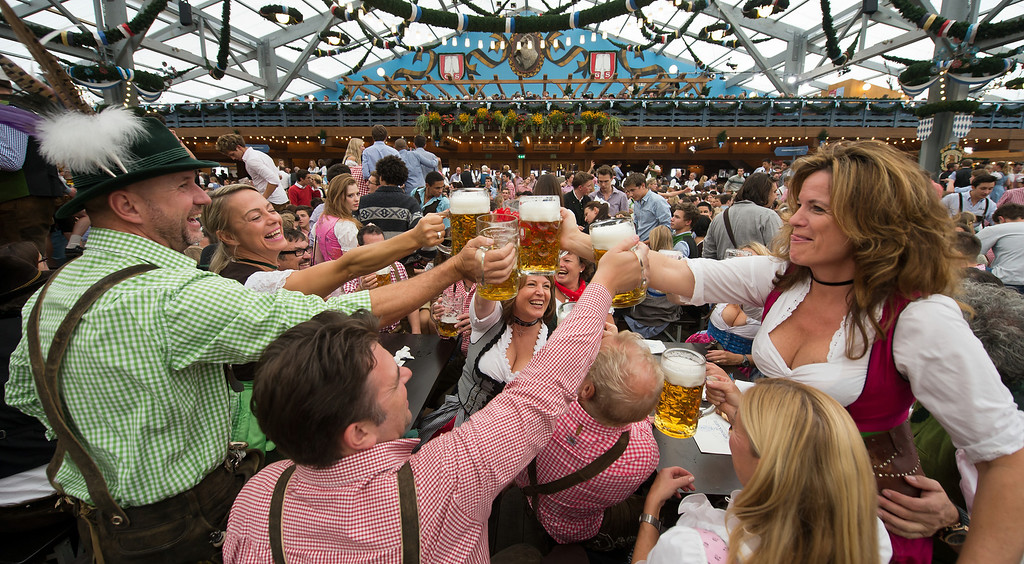 ". Visitors in Bavarian style clothes raise their glasses after getting their first Oktoberfest beer in the Schottenhamel-tent at the Oktoberfest 2013 beer festival at Theresienwiese on September 21, 2013 in Munich, Germany. Shortly before Munich mayor Christian Ude (SPD) had tapped the first barrel with the traditional ""O\'zapft is!\"" (\""It\'s tapped!\"") to launch the festival. The Munich Oktoberfest, which this year will run from September 21 through October 6, is the world\'s largest beer fest and draws millions of visitors. (Photo by Joerg Koch/Getty Images)"