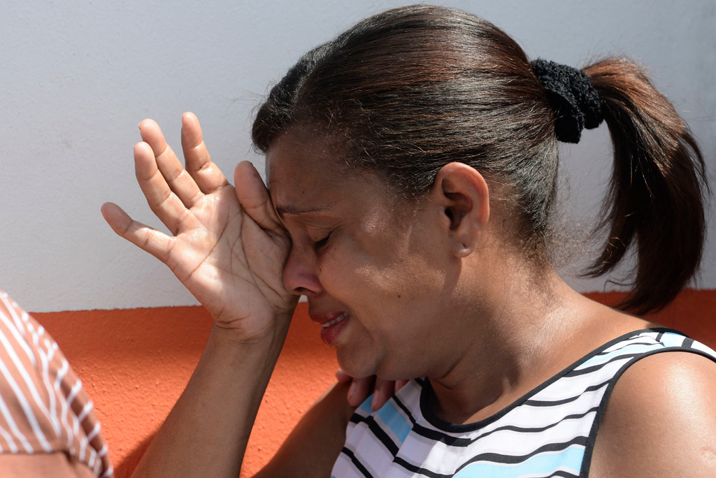 . A woman cries after learning about the arrival of the National Guard at Barrio Obrero in Santurce to distribute water and food among those affected by the passage of Hurricane Maria, in San Juan, Puerto Rico, Sunday, Sept. 24, 2017. Federal aid is racing to stem a growing humanitarian crisis in towns left without fresh water, fuel, electricity or phone service by the hurricane. (AP Photo/Carlos Giusti)