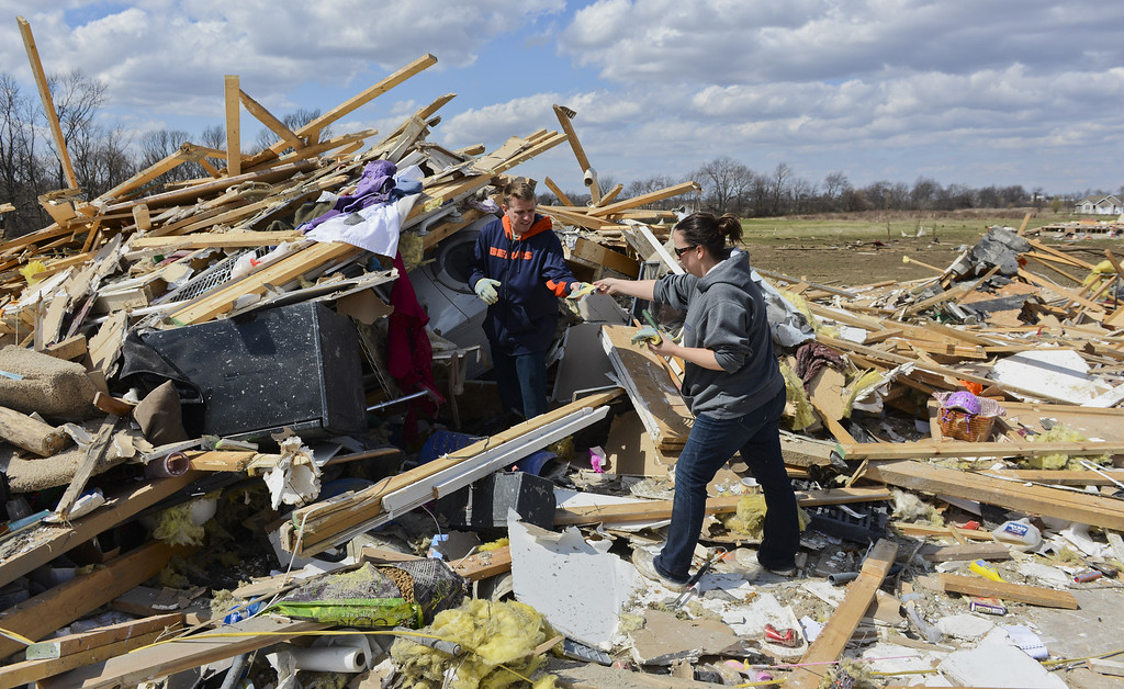 . John Whitaker, left, gets help cleaning remnants of his home from volunteer Jenn Van Hise in the Cherry Hill subdivision outside of Flagg Center, Ill., on Friday, April 10, 2015.  The National Weather Service says at least two tornadoes churned through six north-central Illinois counties. (AP Photo/Matt Marton)